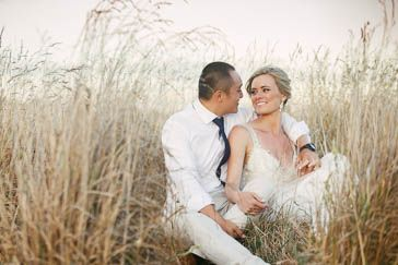 A couple sitting in the long grass at Waverley Estate. Adelaide wedding photography by James Field