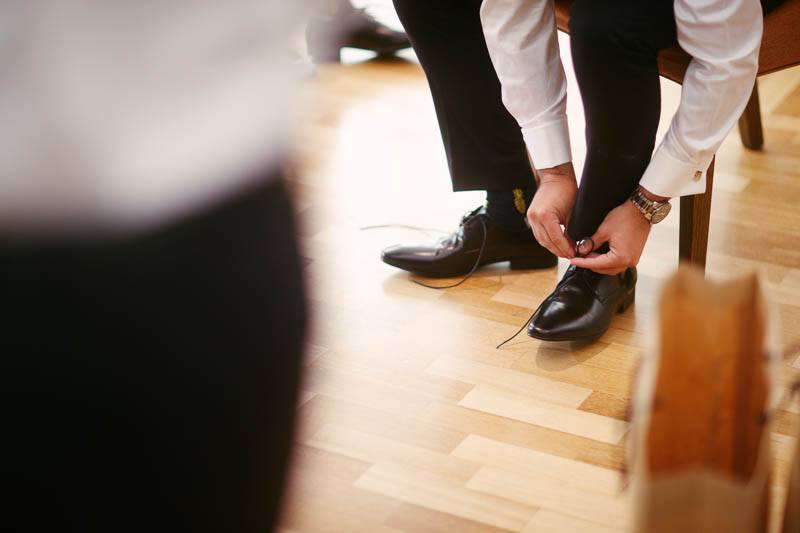 Groom tying his shoes getting ready for the wedding