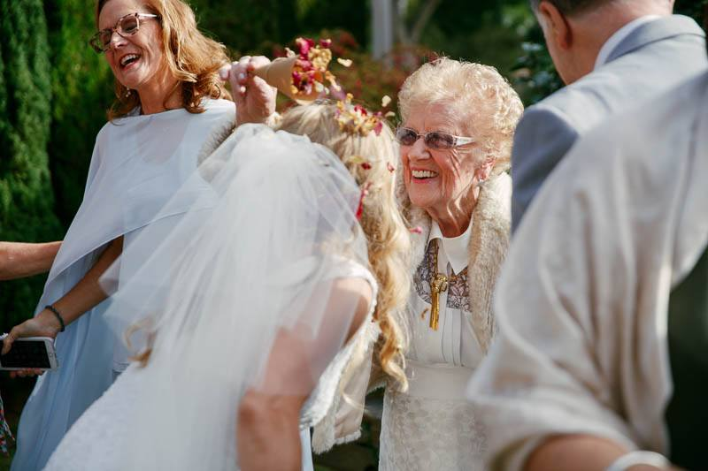 Grandmother throwing petals over the bride