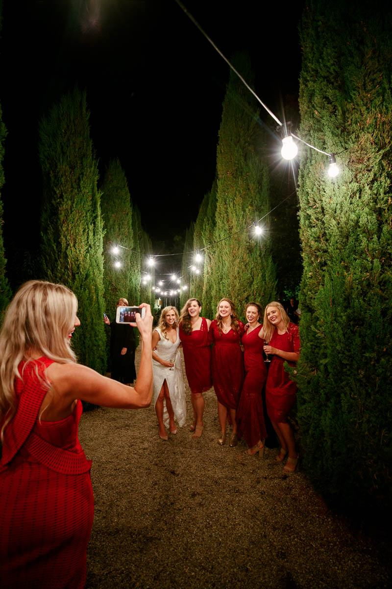 Bridesmaids having their photo taken by a guest outside at night under the festoon lights at Mandalay House and Garden