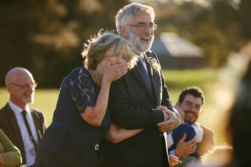 Father and mother of the groom laughing during wedding ceremony