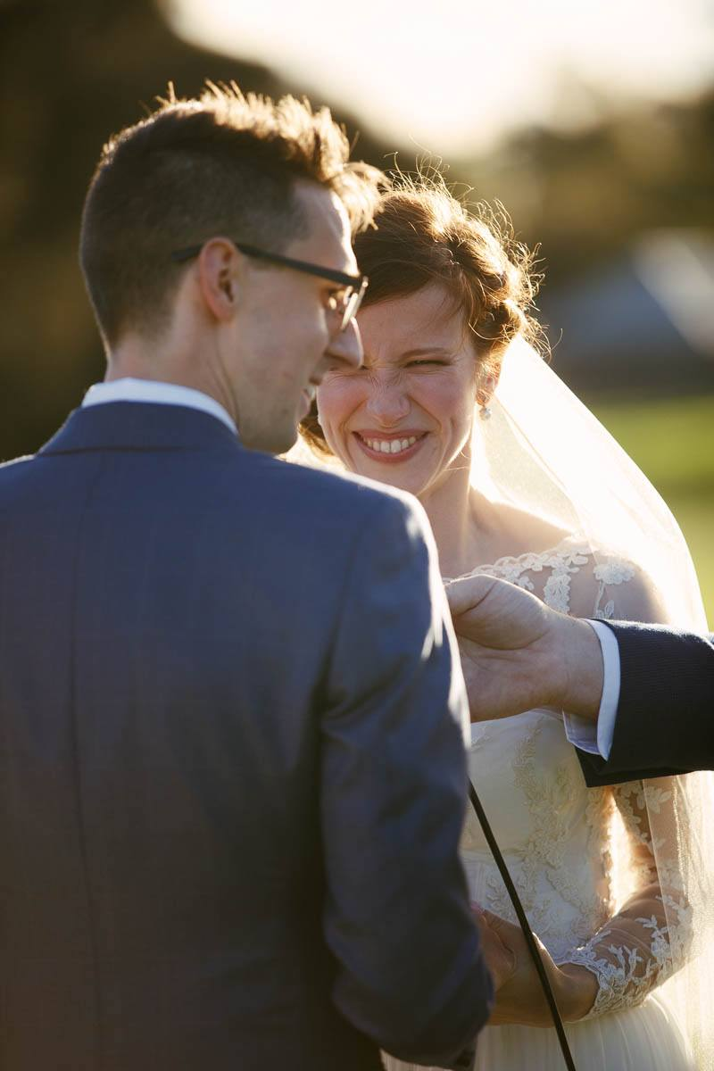 Bride and groom laughing to each other during their wedding