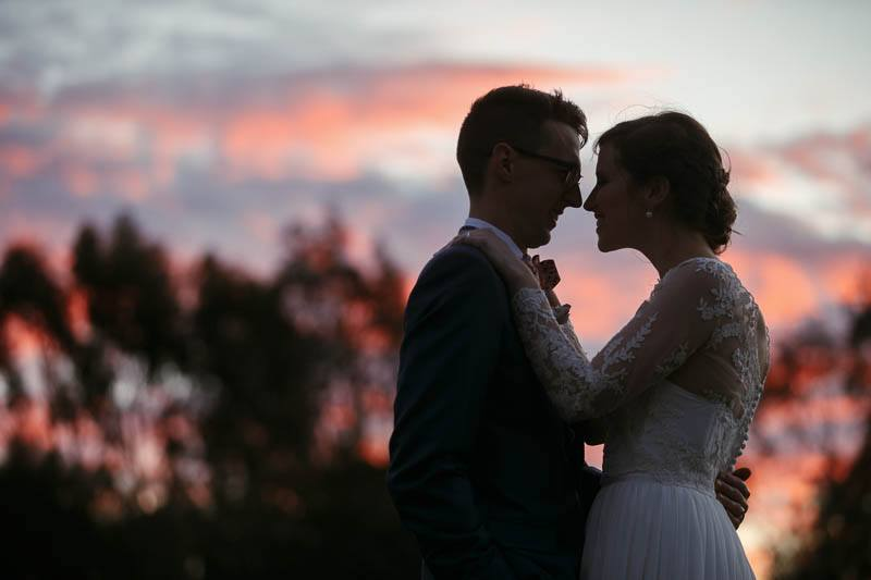 During sunset the bride and groom close together