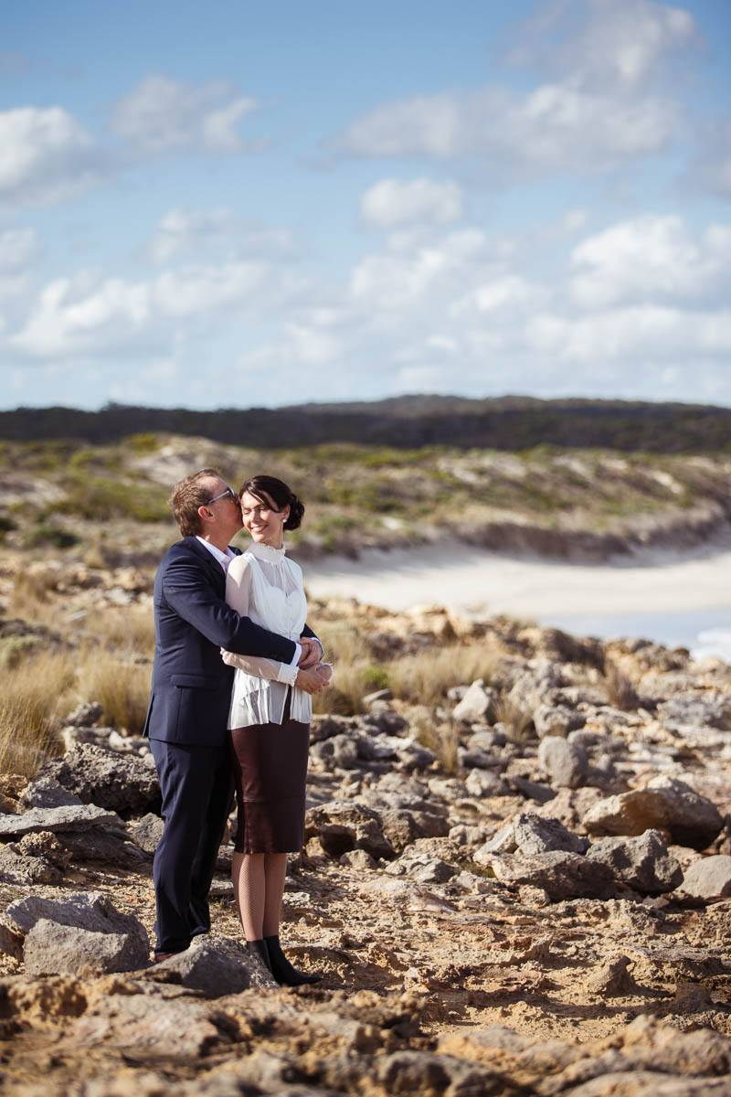 Bride and groom holding each other on the top of the cliffs at Southern Ocean Lodge