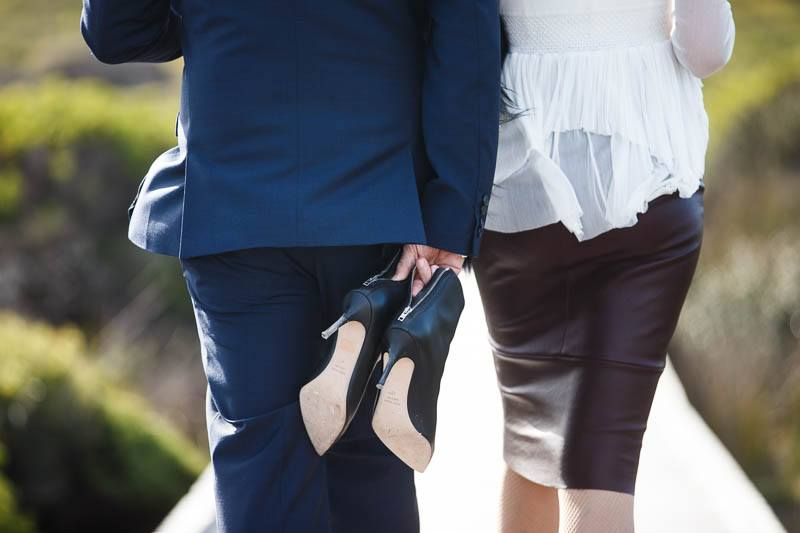 Groom carrying the brides shoes as they walk back from the ceremony along the boardwalk