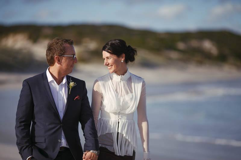 Bride and groom walking along the beach nearby at Hanson Bay