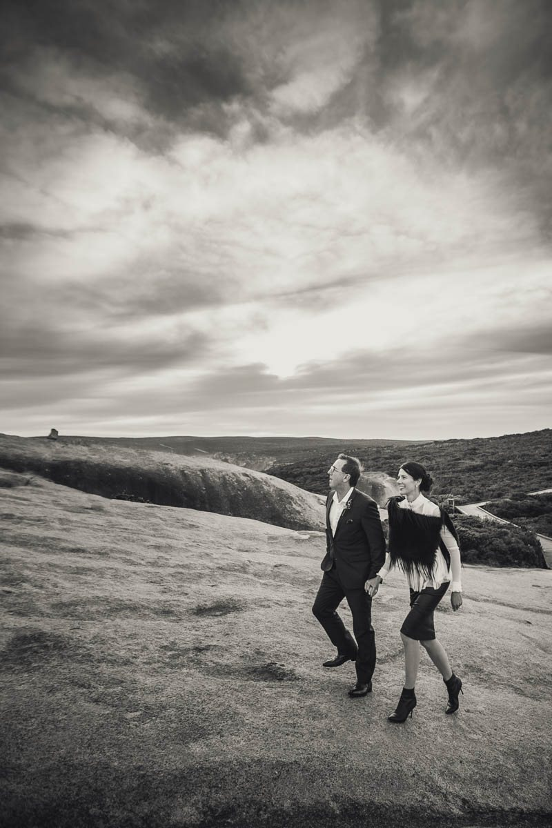Bride and groom walking up the Remarkable Rocks in Kangaroo Island