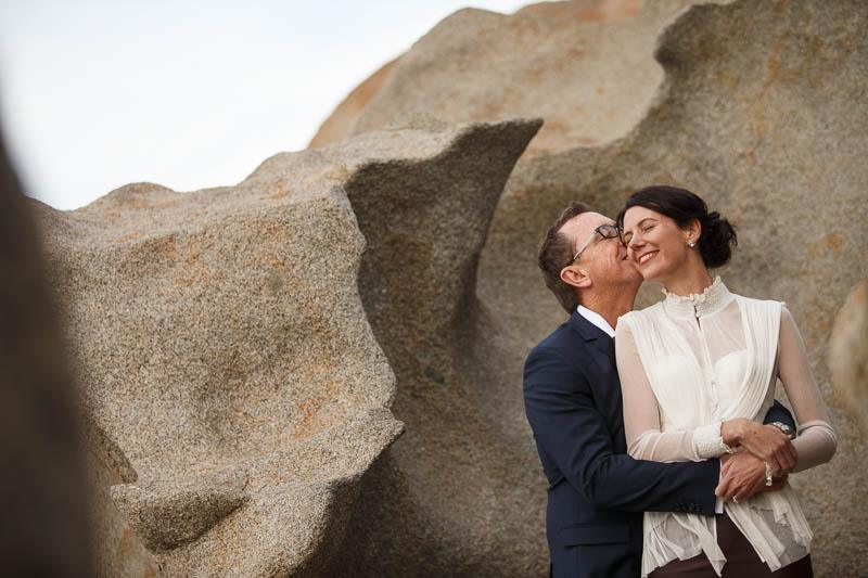 Wedding photography of Kangaroo Island by James Field, the bride and groom at the Remarkable Rocks after a ceremony at the Southern Ocean Lodge