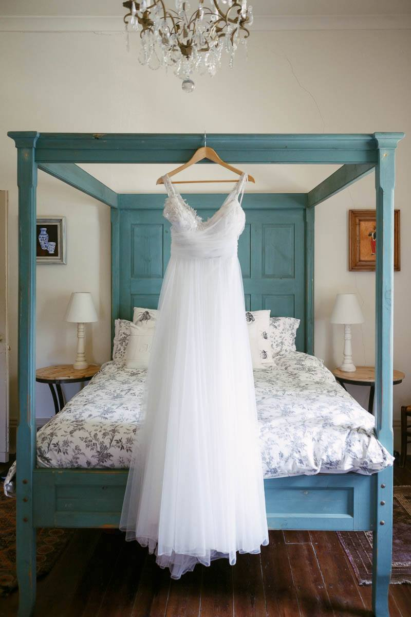 The bride's wedding dress hanging up on the bed at Waverley Estate