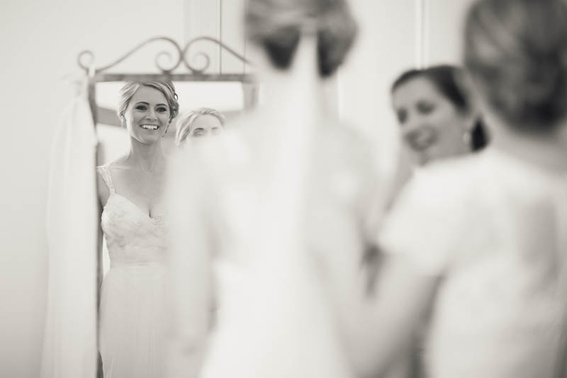 The bride looking at herself after putting the wedding dress on