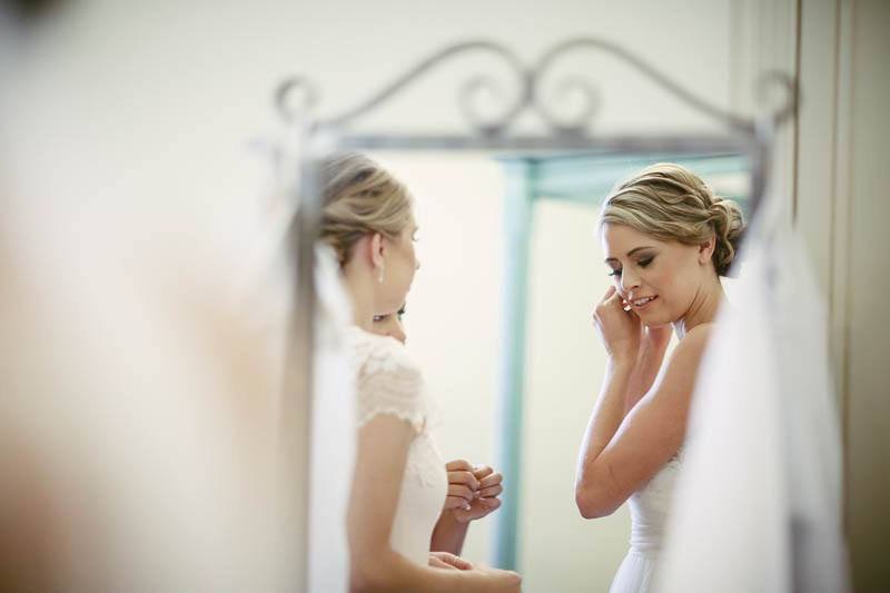 The bride putting her jewelry on just before the wedding