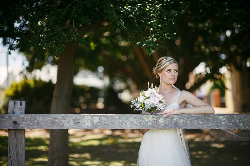 Bride looking out over the fields at Waverley estate, leaning on an old wooden fence