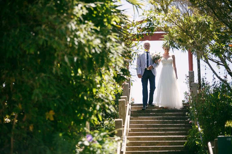 Bride coming down the stairs towards the ceremony with her father