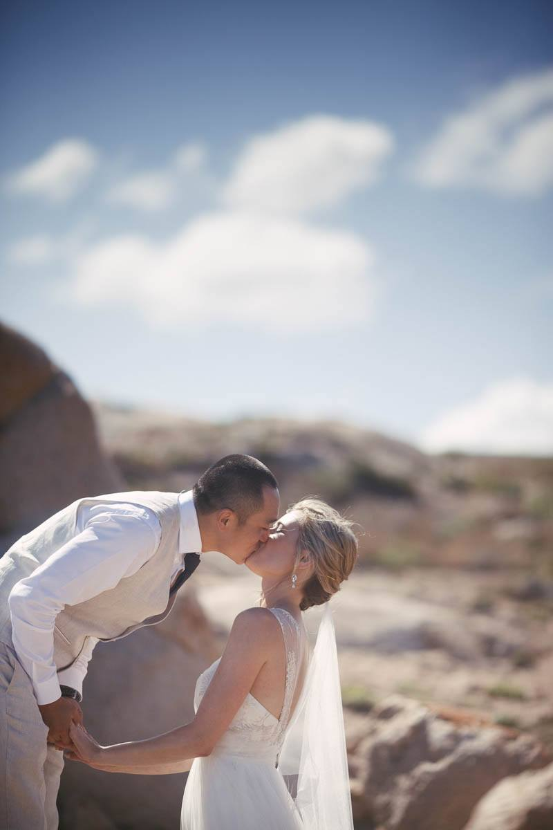 Bride and groom on the cliffs at Port Elliott kissing