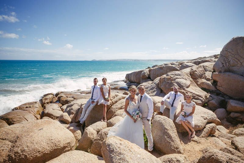 Whole bridal party posing on the top of the cliffs at Port Elliott