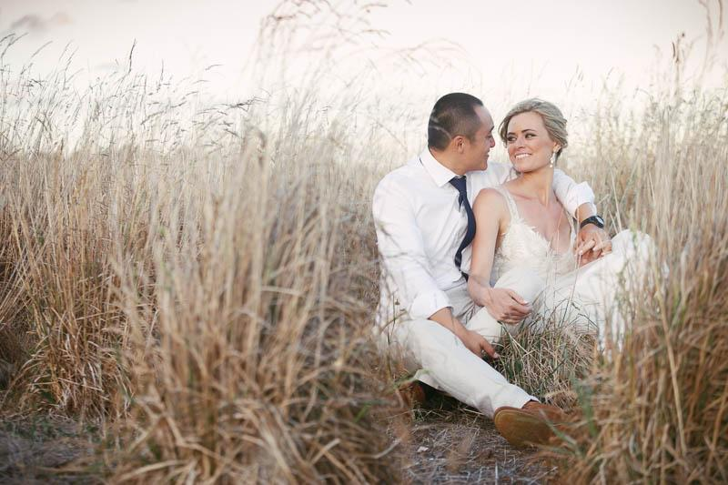 Bride and groom sitting in a field behind Waverley Estate in the long dry grass