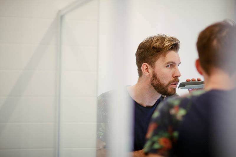 The groom putting the final touches on his beard for his wedding day