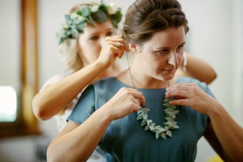 Bridesmaids jewelry adjustments before the wedding ceremony