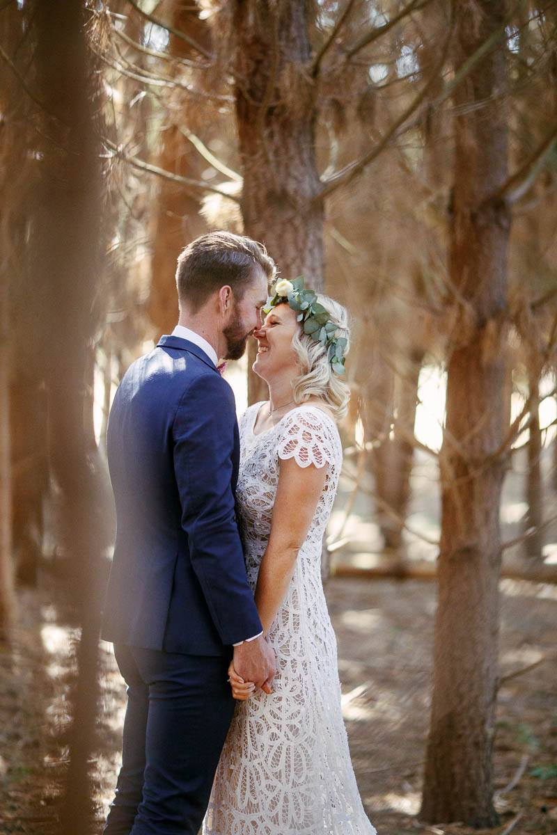 The bride and groom sharing a moment together in the pine forest at Barristers Block