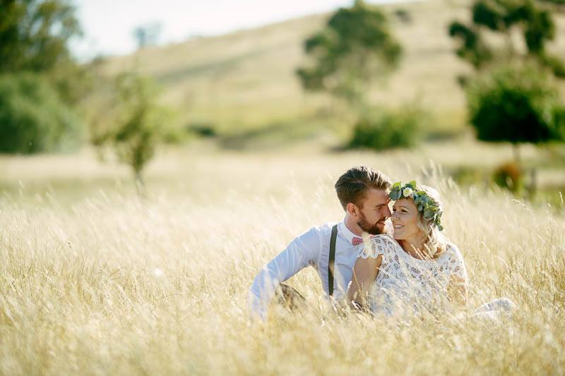 The bride and groom sitting in a field of long dry grass at Barristers Block