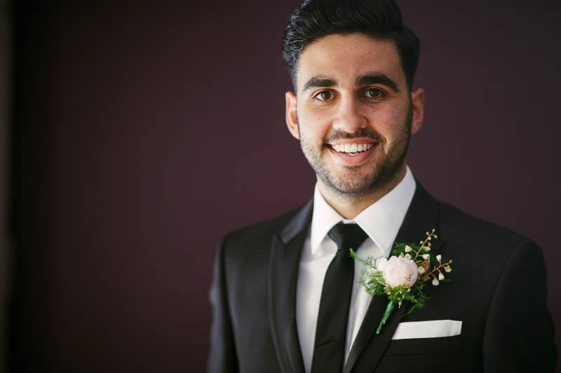 Portrait of the groom against purple wall