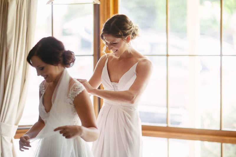 Bridesmaids helping each other prepare for the day