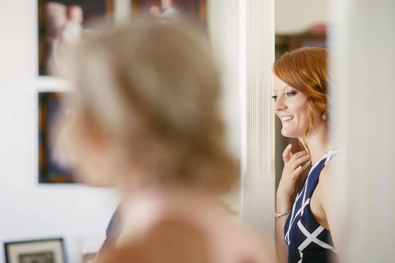 Sister looking on as bride gets dressed