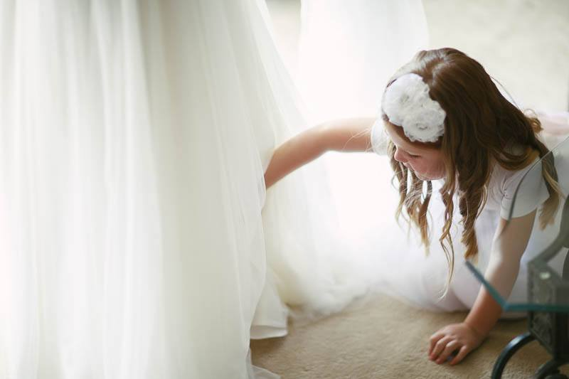 Flower girl helping the bride get dressed
