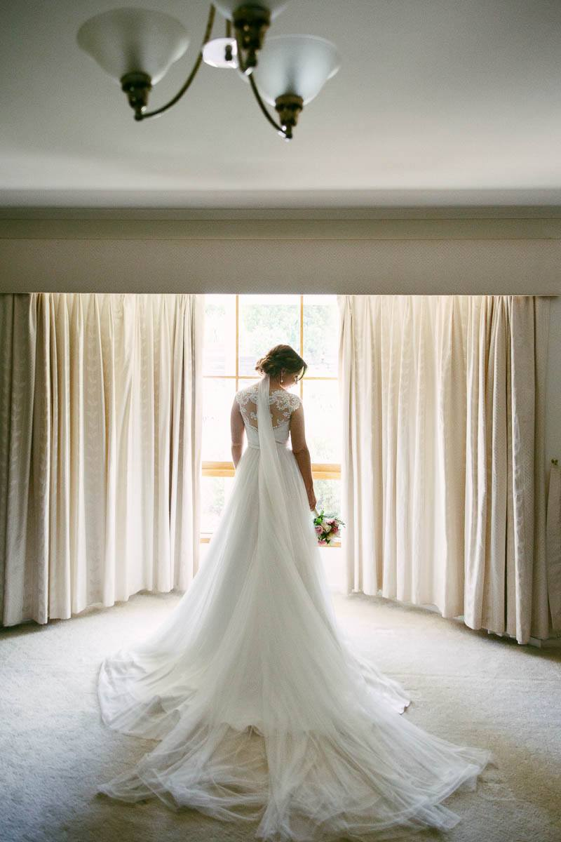 Portrait of the bride in front of the window before leaving for the church