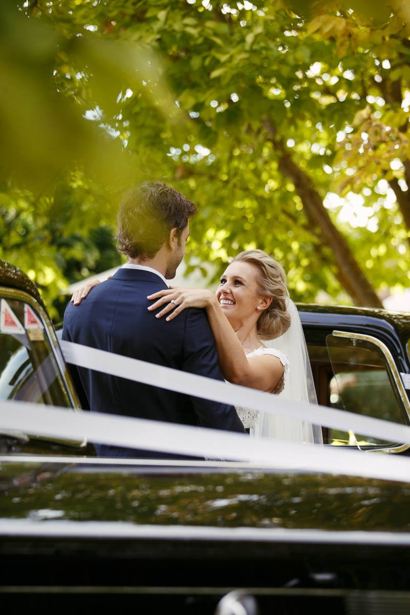 Bride and groom standing between their bridal cars