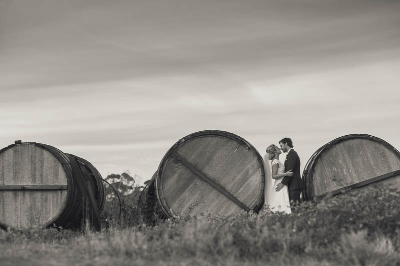 Bride and groom between some large barrels at Golding Wines