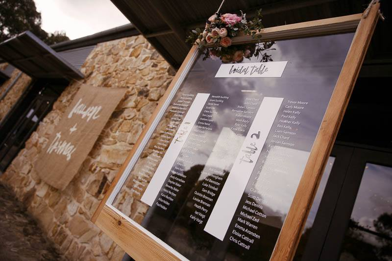 Table places printed on glass hung up outside the reception venue