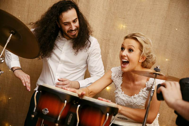 Bride playing bongo drums at Golding Wines. Photography by James Field