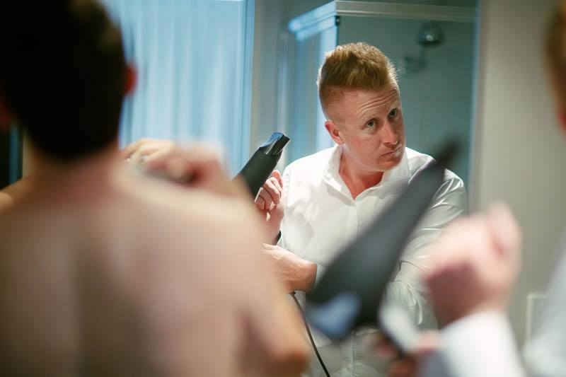 One of the groomsmen blowdrying his hair getting ready for the wedding
