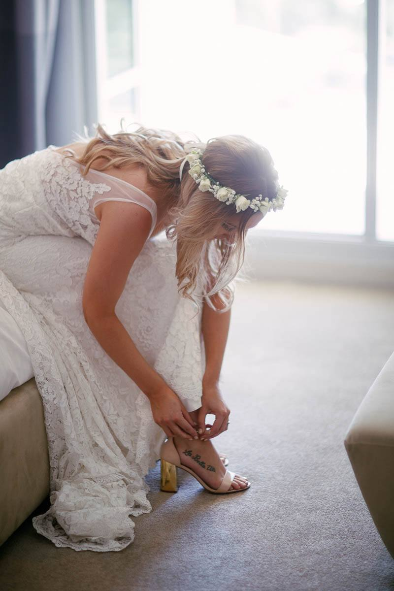 The bride adjusting her shoes before leaving to the wedding at Inglewood Inn