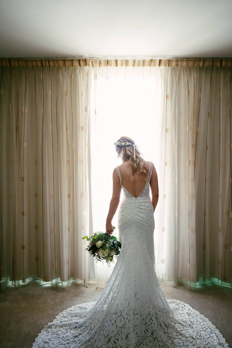 Bride standing by the window before getting ready to leave to Inglewood Inn