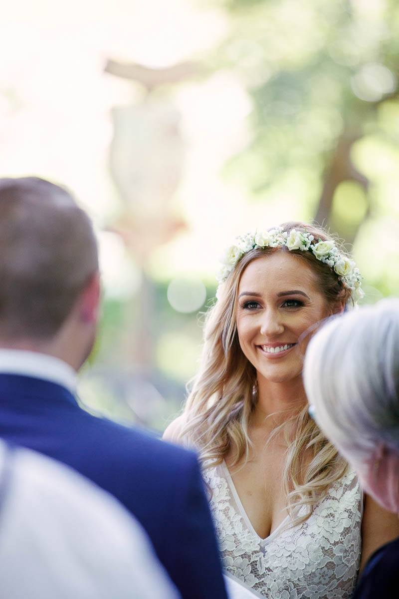 Bride smiling at her groom during the wedding ceremony