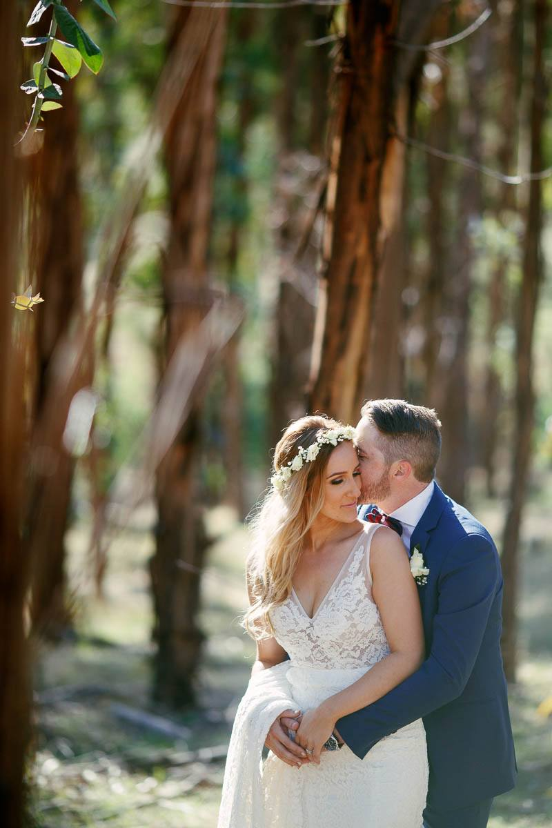 Bride and groom holding each other in a gum tree plantation in a field near Inglewood Inn