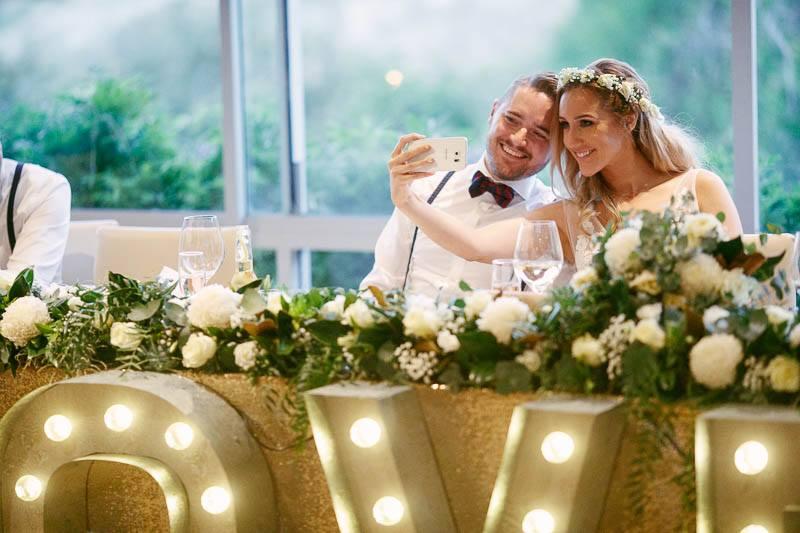 Bride and groom taking wedding day selfies