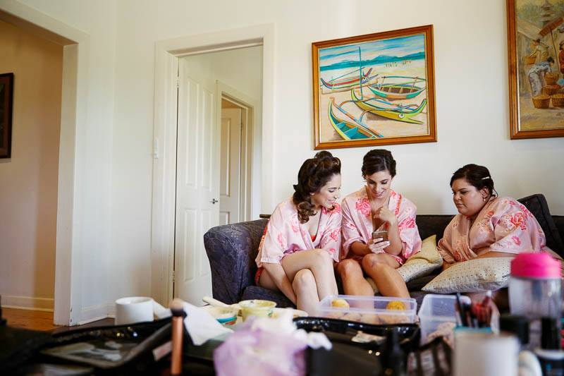 Bridesmaids chatting while hair and makeup preparations are going on