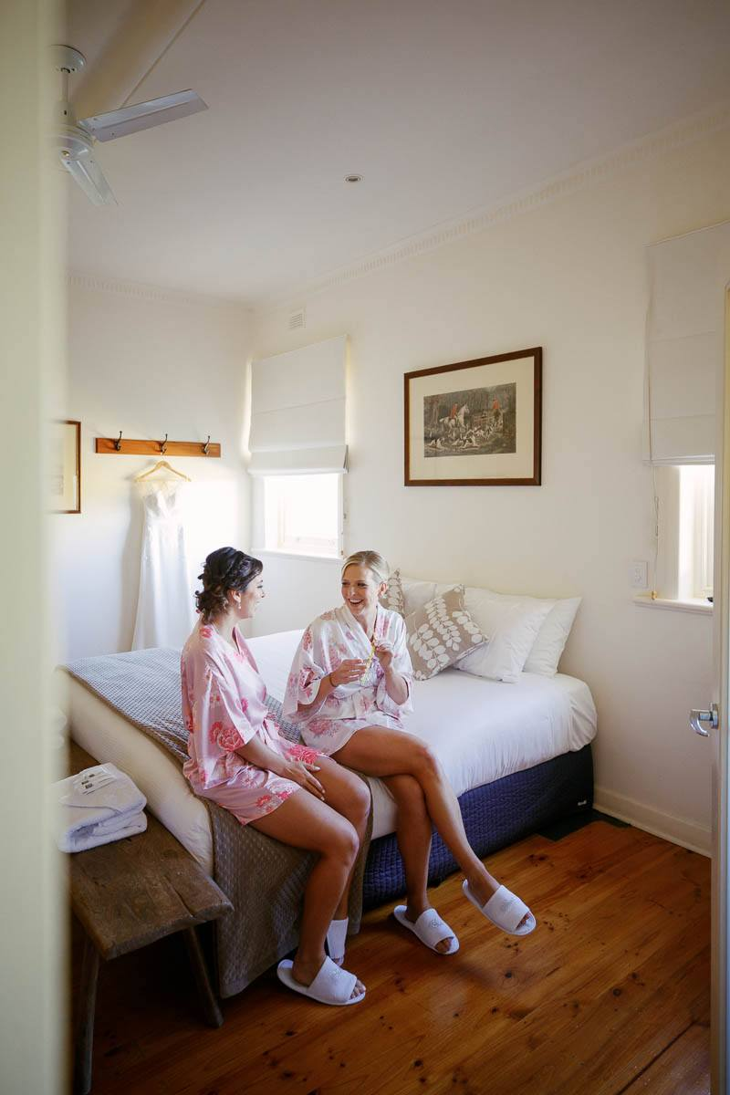 Bride and bridesmaid talking on the bed at Longview Homestead