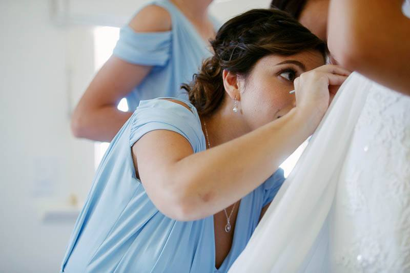 Bridesmaid struggling with the wedding dress buttons