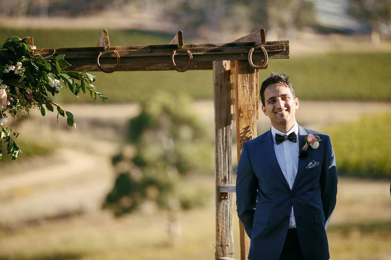 Groom waiting at the end of the aisle for his bride