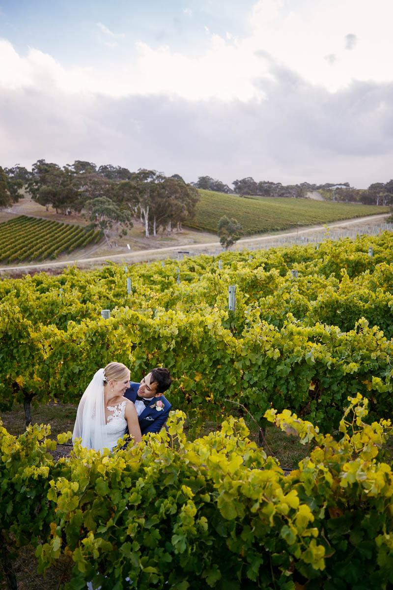 Bride and groom share a candid moment in the vines at Longview Vineyard