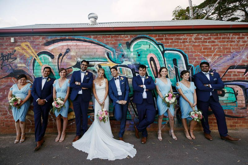Bridal party standing againt a wall of street art
