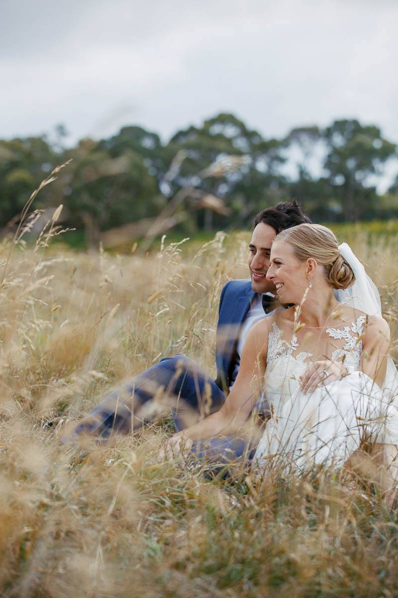 Bride and groom chatting while sitting in the long dry grass