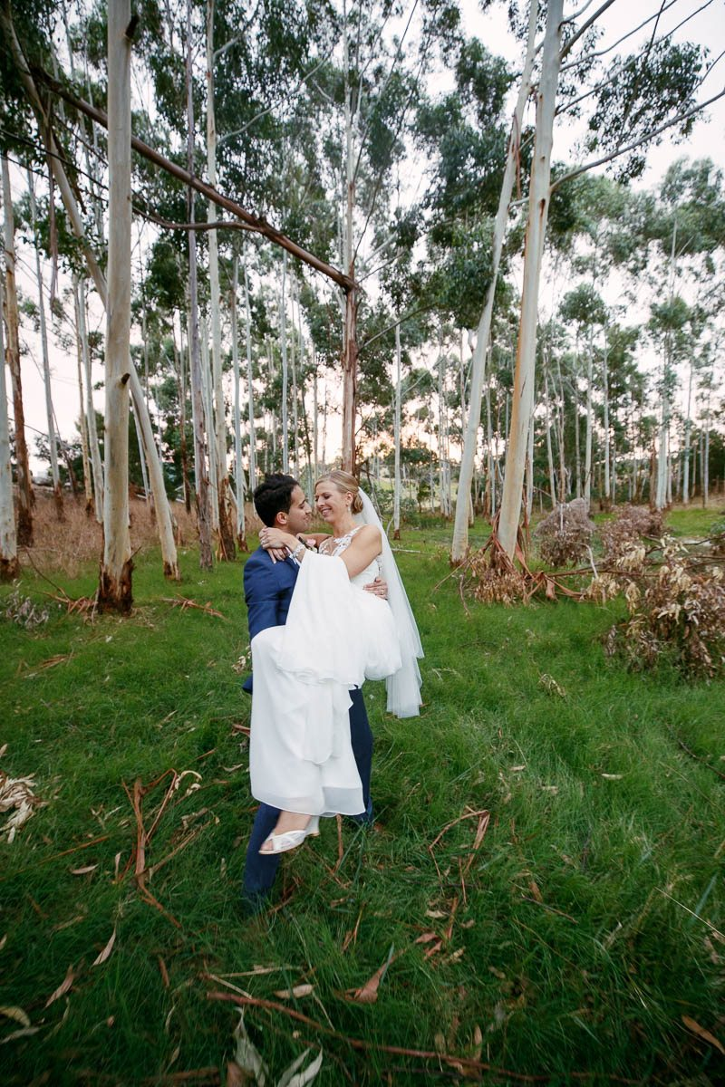Groom carrying his bride in the long grass at Longview Vineyard