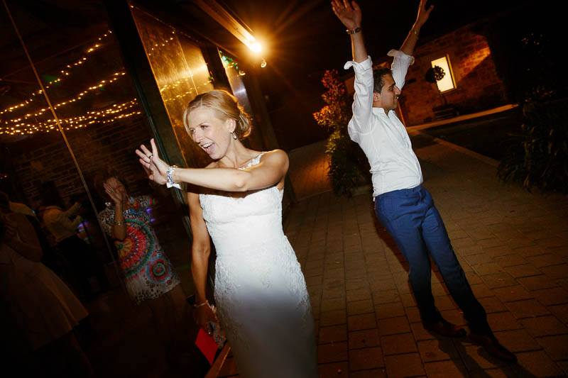 Bride and groom waving goodbye to their guests