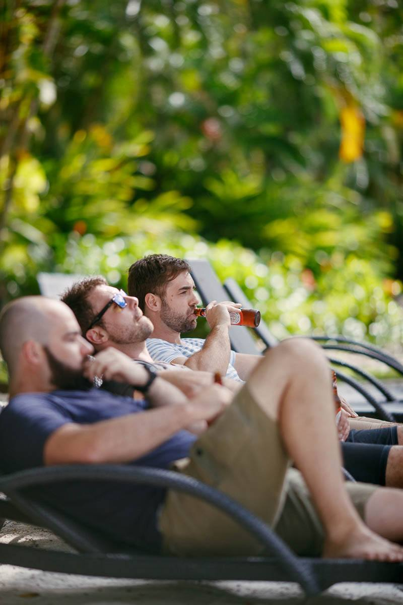 Groomsmen relaxing by the pool enjoying a beer at the Sheraton Mirage in Pt Douglas