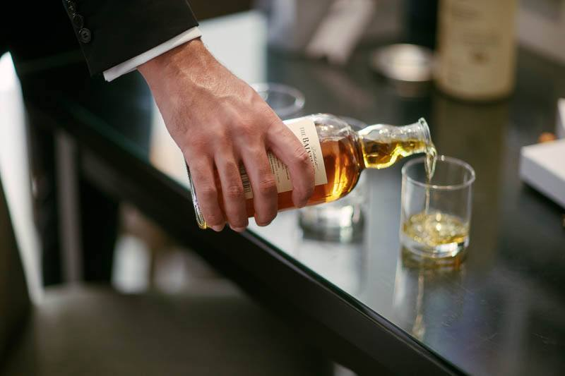 One of the groomsmen pouring a scotch to celebrate the wedding
